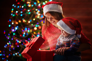 Happy woman and cute little boy in Santa caps looking surprisingly at light from red giftbox