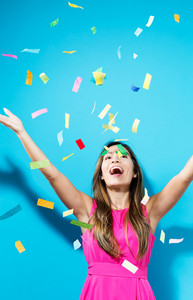 Happy woman celebrating with confetti on a blue background