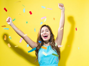Happy woman celebrating with confetti on a yellow background