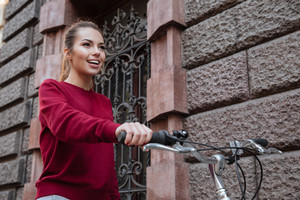 Happy woman dressed in sweater walking with her bicycle near wall and smiling. Look aside.