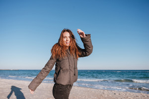 Happy Woman dressed in warm jacket on date on beach near the sea. Side view