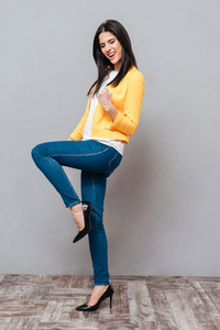 Happy woman dressed in yellow jacket make winner gesture over grey background. Looking down.