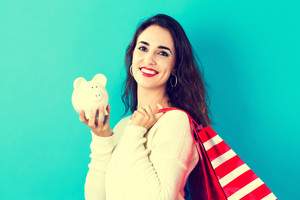 Happy woman holding a piggy bank and shopping bags