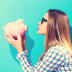 Happy woman holding a piggy bank on a blue background
