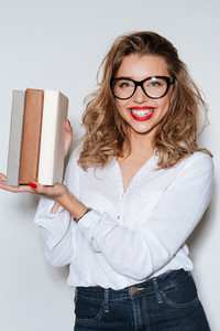 Happy woman holding books in hands and looking at camera over white background