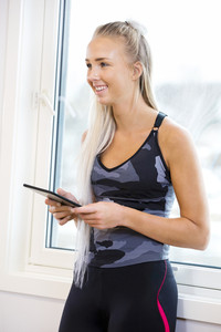 Happy Woman Holding Digital Tablet In Gym
