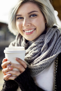 Happy Woman Holding Disposable Coffee Cup At Train Station