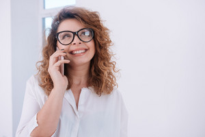 Happy woman in glasses and white shirt talking at phone and looking up over white background