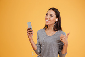 Happy woman in gray sweater listening music on ohone in studio and showing thumb up. isolated orange background