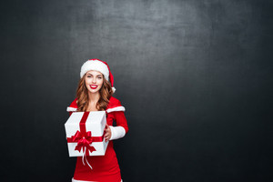 Happy woman in red santa claus outfit holding big white box with a red ribbon isolated on the black background