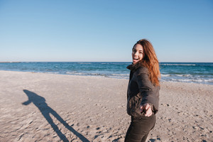 Happy Woman in warm jacket on date on beach near the sea looking at camera