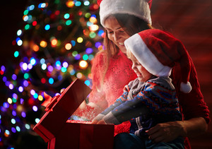 Happy woman looking at her son putting his hands into magic red giftbox with golden dust