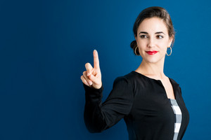 Happy woman pointing to something on a dark blue background