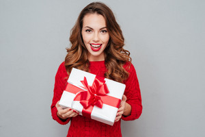 Happy woman red sweater holding a white box with a red ribbon