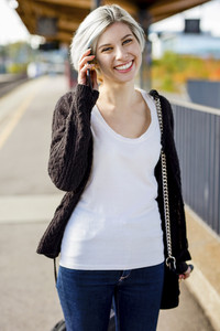 Happy Woman Talking On Mobile Phone At Railroad Platform