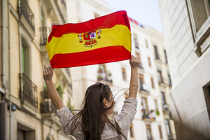 Happy woman tourist is walking in the city street of Barcelon with spanish flag.