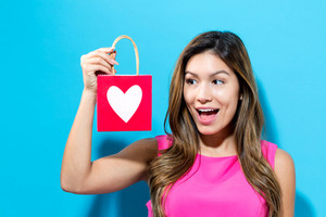 Happy woman with a gift bag with a heart print