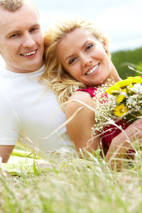 Happy woman with bunch of flowers and her boyfriend looking at camera