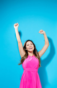 Happy woman with her arms outstreched on a blue background