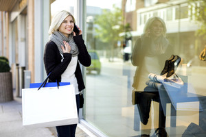 Happy Woman With Shopping Bags Using Mobile Phone Outside Boutiq