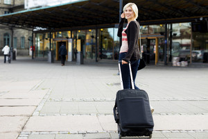 Happy Woman With Wheeled Luggage Walking Towards Train Station
