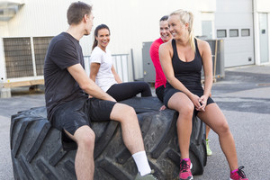 Happy workout team sitting on a tire and taking a break outdoor