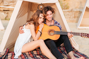 Happy young beautiful couple sitting with guitar on the beach at the tent