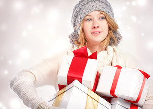 Happy young blonde woman holding many gift boxes