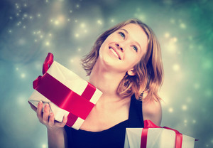 Happy young blonde woman holding present boxes