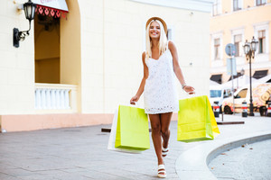 Happy young blonde woman in hat holding shopping bags while walking on the street