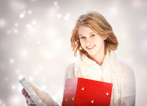 Happy young blonde woman opening a big red present box
