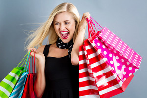 Happy young blonde woman with shopping bags on a gray background