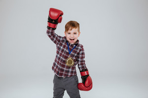 Happy Young boy in boxing gloves with open mouth looking at camera. Isolated gray background