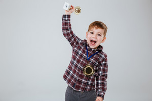 Happy young boy in shirt holding chalice and looking at camera with open mouth. Isolated gray background