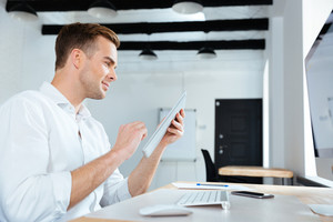 Happy young businessman sitting and using tablet in office
