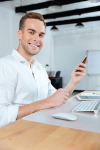Happy young businessman working and using smartphone in office