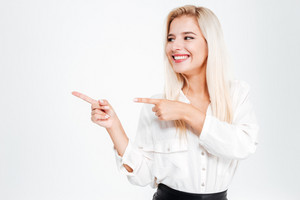 Happy young businesswoman pointing fingers away at copyspace isolated on white background