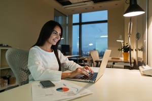Happy young businesswoman working with laptop in office