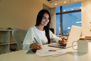 Happy young businesswoman writing and working with laptop in office