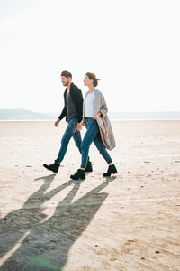 Happy young casual couple holding hands and walking on the beach