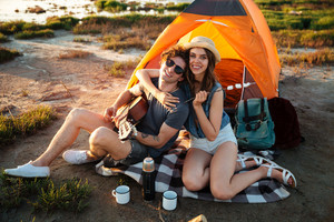 Happy young cheerful couple having fun camping by a lake