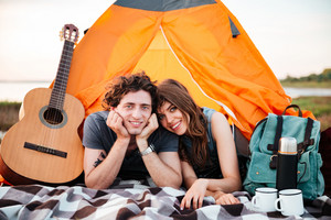 Happy young couple camping on the beach laying in the tent
