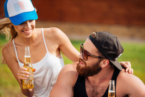 Happy young couple drinking beer and laughing outdoors in summer