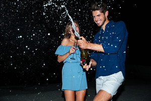 Happy young couple drinking champagne and having fun at night on the beach