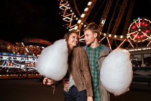 Happy young couple eating cotton candy in amusement park. in warm clothes