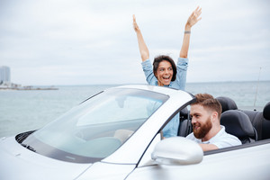 Happy young couple enjoying road trip in their white convertible