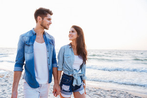 Happy young couple holding hands and walking on the beach