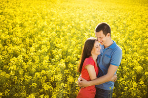 Happy young couple in love hugging in yellow colza field