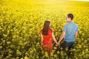 Happy young couple in love is walking and holding hands in yellow colza field