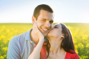 Happy young couple in love kissing in yellow colza field